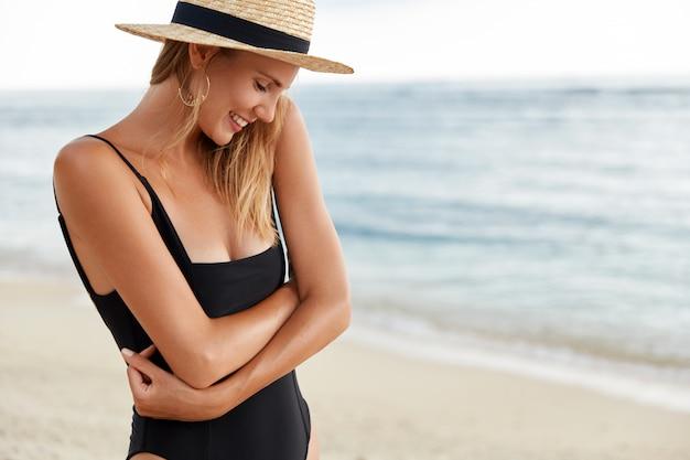 Zdjęcie nieśmiałej ładnej kobiety trzymającej ręce skrzyżowane, ubrana w czarne bikini i słomkowy kapelusz, pozuje szczęśliwie nad błękitnym oceanem, demonstruje zdrową, czystą skórę, szczęśliwą, że została sfotografowana. ludzie, czas wolny, lato