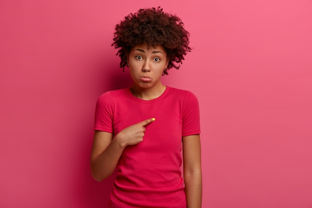 Zdjęcie nieszczęśliwej młodej afroamerykanki wskazuje na siebie z żałosnym wyrazem twarzy, pyta, dlaczego jestem winny, ściąga dolną wargę ze złych emocji, nosi szkarłatną koszulkę, wspomina o smutku