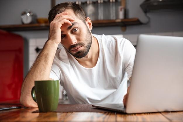 Zdjęcie niezadowolonego 30-letniego mężczyzny w swobodnej koszulce na srebrnym laptopie, siedzącego przy stole w nowoczesnym mieszkaniu