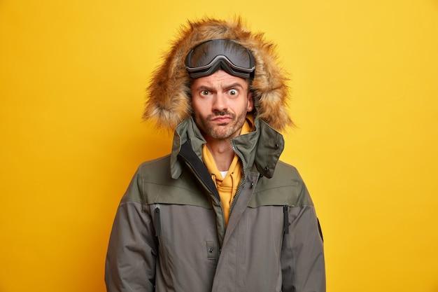Zdjęcie niezadowolonego mężczyzny z aktywnym zimowym odpoczynkiem wygląda z poirytowanym wyrazem unosząc brwi ubrany w ciepłą kurtkę termoaktywną z kapturem.