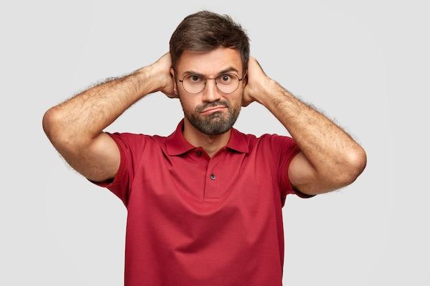 Zdjęcie niezadowolonego, nieogolonego mężczyzny marszczy brwi i patrzy ze złością