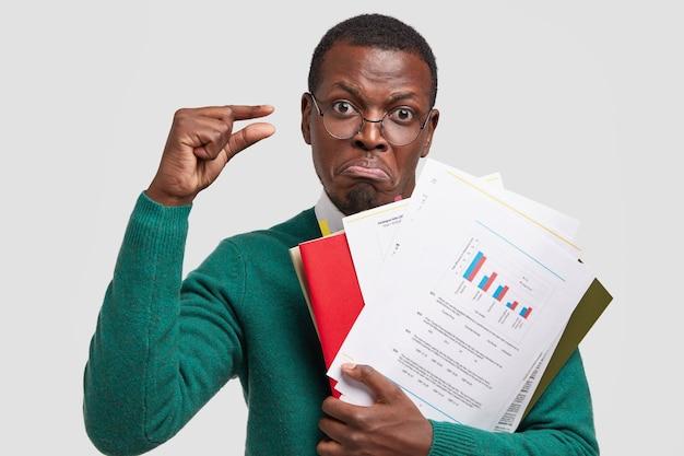 Zdjęcie niezadowolonego właściciela firmy o ciemnej karnacji, analizującego dane informacyjne w dokumentach, pokazuje mały gest