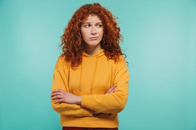 Zdjęcie niezadowolonej kobiety w wieku 20 lat z kręconymi rudymi włosami, patrzącej na bok z rękami skrzyżowanymi na białym tle nad niebieską ścianą