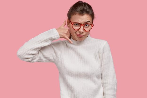 Zdjęcie niezadowolonej kobiety wykonuje gest wezwania, pyta chłopaka o oddzwonienie, gesty na odległość, marszczy brwi