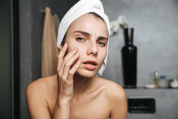 Zdjęcie niezadowolonej kobiety z ręcznikiem na głowie dotykającej jej twarzy po kąpieli