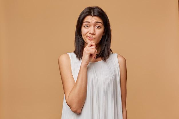 Zdjęcie niezadowolonej opalonej kobiety w białej sukni stojącej z ręką trzymającą brodę, marszczącej brwi, wyrażającej podejrzliwość i nieporozumienie,