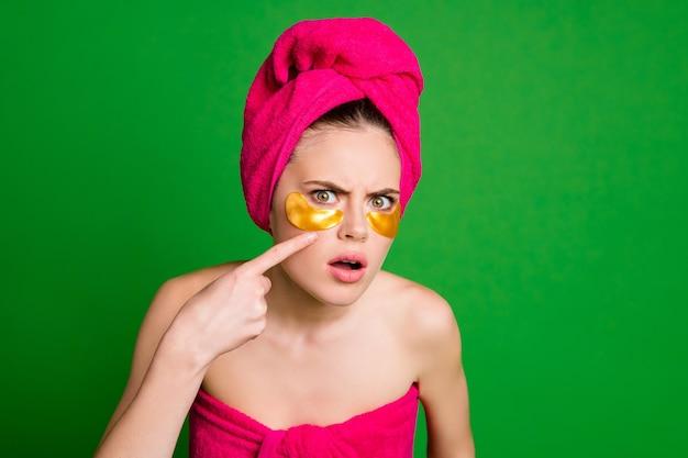 Zdjęcie niezadowolonej pani używa łatek pod oczami spojrzenie lustro niechęć złych ręczników do skóry ciało głowa odizolowany zielony kolor tła