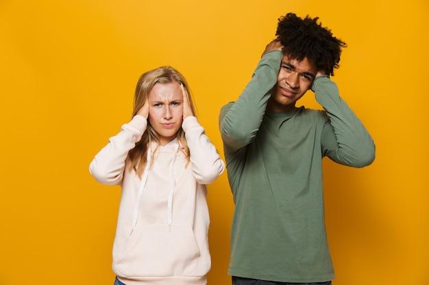 Zdjęcie niezadowolonej pary mężczyzny i kobiety w wieku 16-18 lat z aparatami ortodontycznymi zakrywającymi uszy, odizolowane na żółtym tle