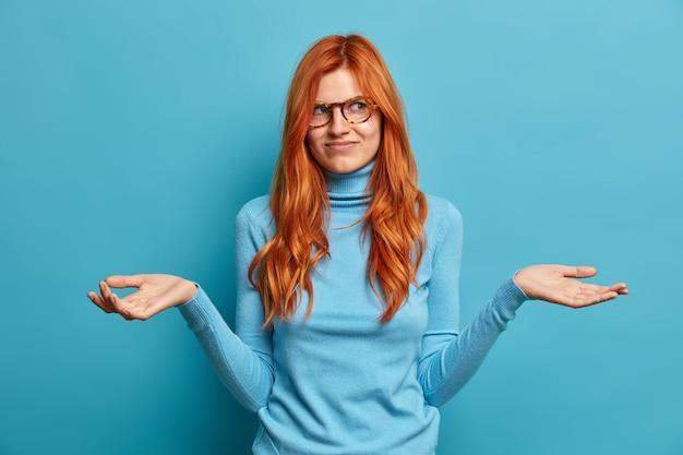 Zdjęcie obojętnej, przystojnej kobiety z długimi rudymi włosami rozpościera dłonie i wygląda nieświadomie, nie może zdecydować, co robić, ubrana w zwykły strój.