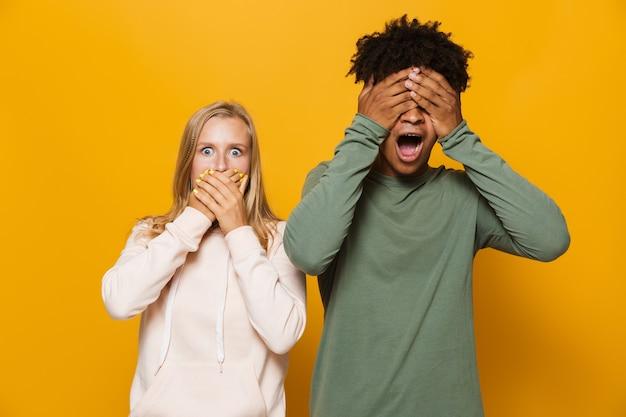 Zdjęcie oburzonej pary mężczyzny i kobiety 16-18 lat z aparatami ortodontycznymi zakrywającymi twarze rękami, odizolowane na żółtym tle