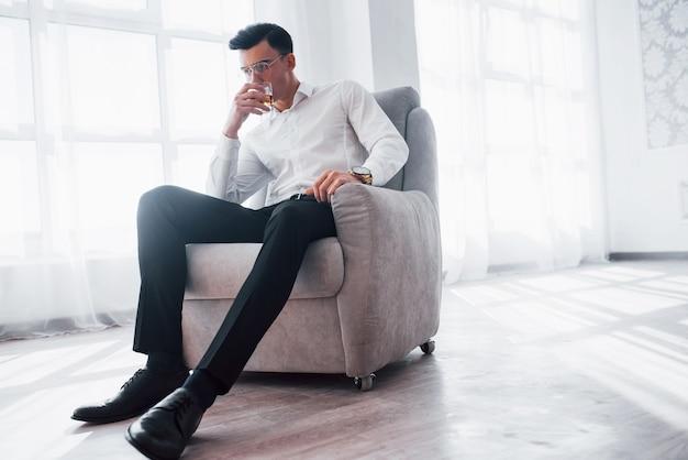 Zdjęcie od dołu. luksusowo wyglądający mężczyzna w klasycznym stroju siedzący na krześle w pokoju i trzymający szklankę z alkoholem.