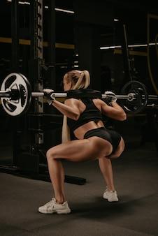 Zdjęcie od tyłu wysportowanej kobiety o blond włosach, która kuca ze sztangą w pobliżu stojaka do przysiadów na siłowni