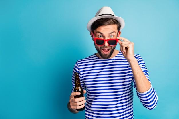 Zdjęcie odjazdowego miłego podróżnika pije butelkę piwa all inclusive egzotyczny kurort zobacz baner reklamowy ceny zakupów nosić okulary przeciwsłoneczne w paski marynarska koszula czapka na białym tle niebieski kolor
