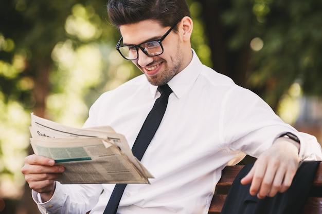 Zdjęcie odnoszącego sukcesy mężczyzny w garniturze siedzącego na ławce w zielonym parku i czytającego gazetę w słoneczny dzień