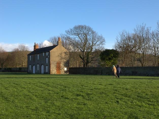 Zdjęcie ogrodzenia dwie osoby spacerujące po ogrodzonym trawniku w kierunku starego budynku
