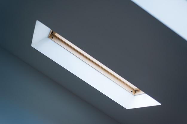 Zdjęcie okna na poddaszu, światło wpada do pokoju.