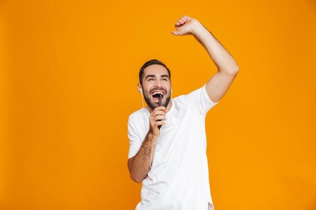 Zdjęcie optymistycznego człowieka 30s słuchania muzyki przez słuchawki i telefon komórkowy, na białym tle