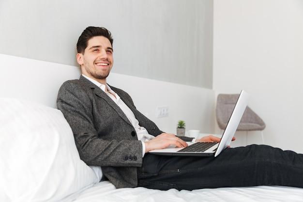 Zdjęcie optymistycznego mężczyzny w biznesowych ubraniach uśmiechniętych i patrząc na bok, leżąc w łóżku z laptopem