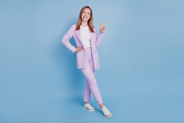 Zdjęcie optymistycznej damy pokazuje znak v na białym tle na niebieskim tle