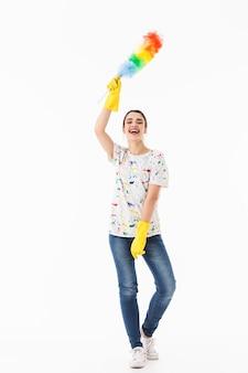 Zdjęcie optymistycznej kobiety w wieku 20 lat w żółtych gumowych rękawiczkach do ochrony rąk, trzymającej kolorową ściereczkę podczas sprzątania pokoju na białym tle nad białą ścianą