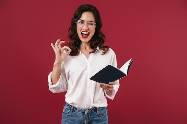 Zdjęcie optymistycznej młodej kobiety w okularach pokazujący gest porządku na białym tle na czerwonej ścianie trzymając notebook.