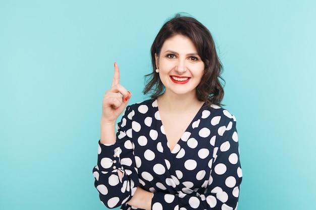 Zdjęcie osoby płci żeńskiej pokazując jej palec i uśmiechając się na białym tle nad niebieskim backgrownd.