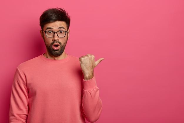 Zdjęcie oszołomionego młodego brodatego mężczyzny wskazuje z prawej strony, pokazuje coś niesamowitego, wzdycha ze zdziwienia, nosi okulary i swobodny sweter, pozuje na różowej ścianie. koncepcja promocji