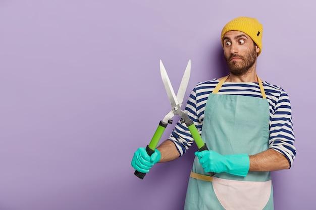 Zdjęcie oszołomionego ogrodnika pozującego z dużymi nożycami