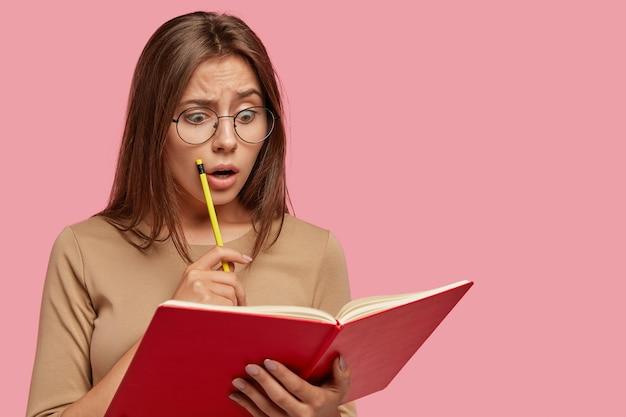 Zdjęcie oszołomionej atrakcyjnej kobiety czyta szokujące informacje w podręczniku, trzyma ołówek, trzyma szeroko otwarte usta