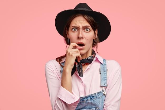 Zdjęcie oszołomionej kobiety wygląda ze zdumieniem, trzyma palec przy otwartych ustach