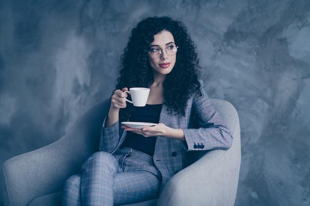 Zdjęcie pani biznesu siedzieć w fotelu do picia espresso na białym tle nad szarą ścianą