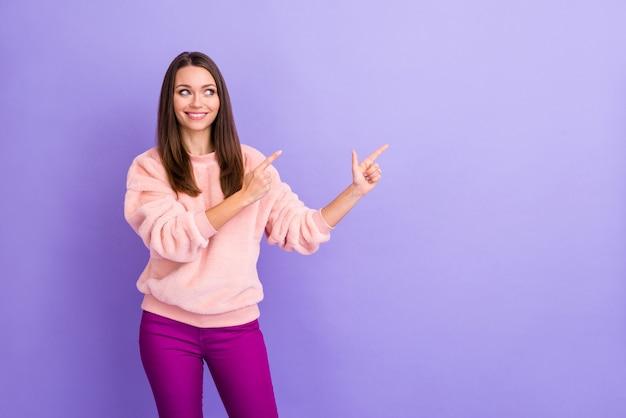 Zdjęcie pani wskazującej palce wyglądają na puste miejsce na fioletowej ścianie
