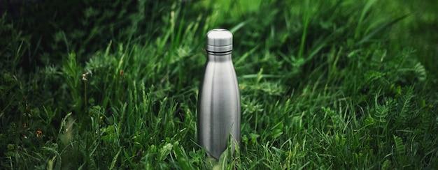 Zdjęcie panoramiczne stalowej butelki termo wielokrotnego użytku w zielonej trawie.