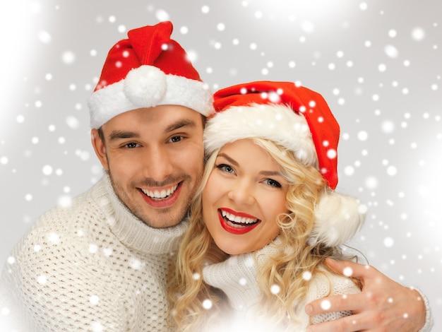 Zdjęcie pary rodzinnej w swetrach i czapkach świętego mikołaja