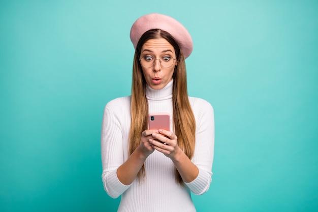 Zdjęcie patrząc atrakcyjna pani trzymać telefon czytanie nowego postu negatywne komentarze nosić specyfikacje nowoczesny różowy beret czapka biały golf na białym tle jasny turkusowy kolor tła