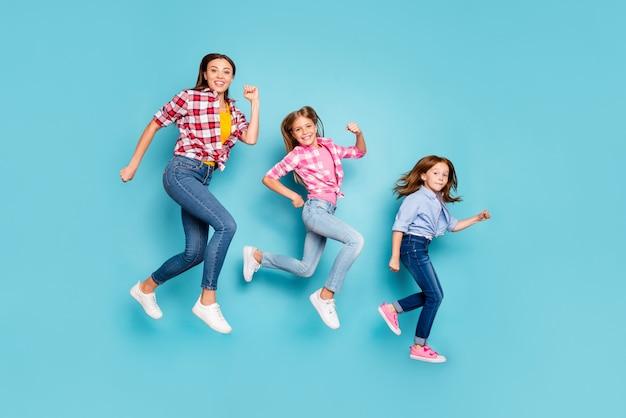Zdjęcie pełnej długości ciała przedstawiające radującą się wesołą, radosną białą rodzinę pin-up biegnącą po sobie w dżinsach, odizolowanych na niebieskim tle