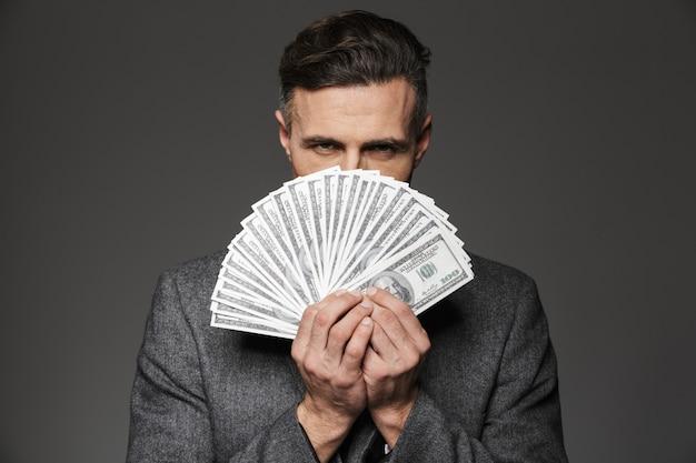 Zdjęcie pewnego siebie 30-letniego faceta w garniturze z fanem banknotów dolarowych na twarzy i surowym spojrzeniem, odizolowane na szarej ścianie