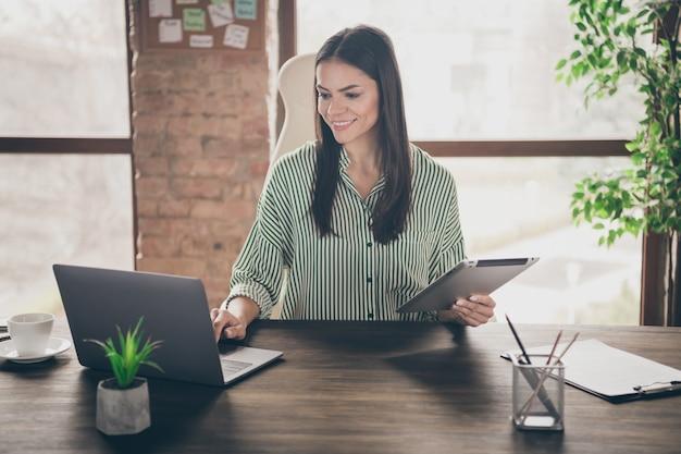 Zdjęcie pewnej biznesowej pani siedzieć na biurku w biurze trzymać tablet, wpisując w notatniku