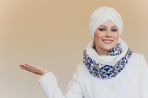 Zdjęcie pewnej siebie arabskiej damy w hidżabie, pokazuje właściwą drogę, wskazuje pustą przestrzeń obiema palcami, zaprasza tam, promots kopiuje przestrzeń. sprawdź to ze mną.