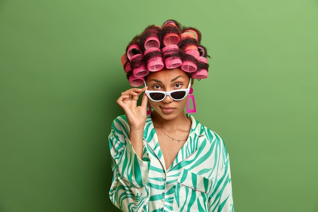 Zdjęcie pewnej siebie ciemnoskórej kobiety wygląda z okularów przeciwsłonecznych, ma pewne siebie spojrzenie, uważnie słucha kogoś, układa idealne loki z lokówkami, przygotowuje się do uczczenia wyjątkowej okazji w życiu