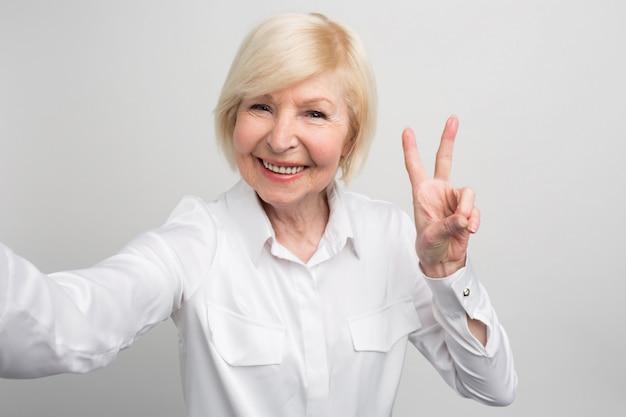 Zdjęcie pewnej siebie i nowoczesnej babci, która lubi robić selfie. wie wszystko o nowych trandach na świecie. a jej wiek nie przeszkadza.