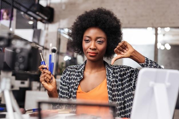Zdjęcie. piękna ciemnoskóra kobieta z kręconymi włosami uśmiecha się podczas pozowania do kamery