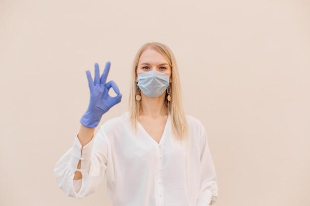 Zdjęcie piękna młoda kobieta stojąca w medycznej masce i rękawiczkach lateksowych niebieskie