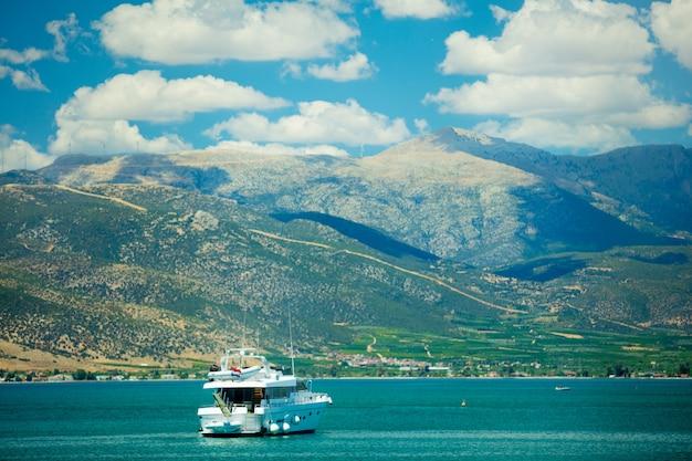 Zdjęcie pięknego statku na morzu w cudownych górach w grecji