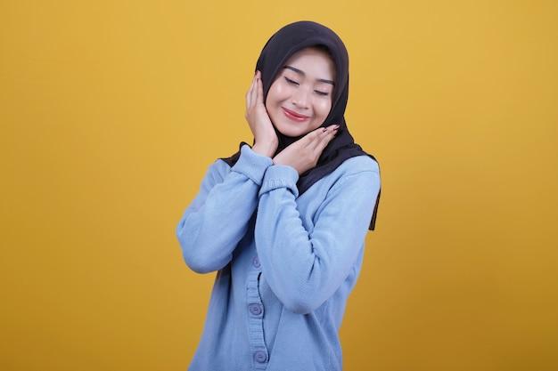 Zdjęcie pięknej azjatki unoszącej ręce w górę, noszącej czarny hidżab, gdzieś szczęśliwie spogląda, bawi się i zamyka oczy
