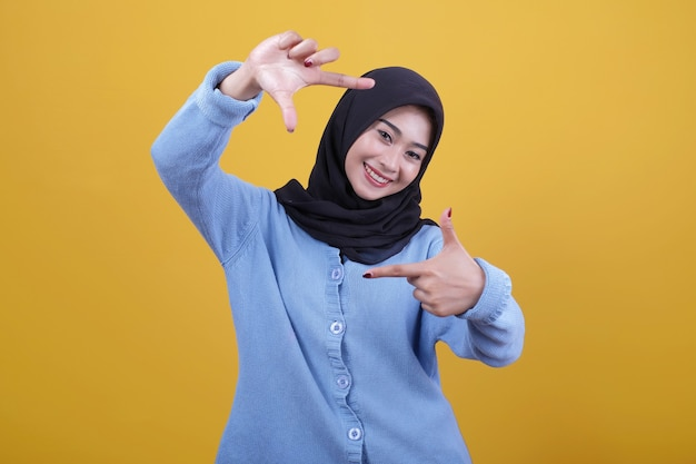 Zdjęcie pięknej azjatki unoszącej ręce w górę, noszącej gdzieś szczęśliwie czarne hidżabowe spojrzenia, ma zabawny gest