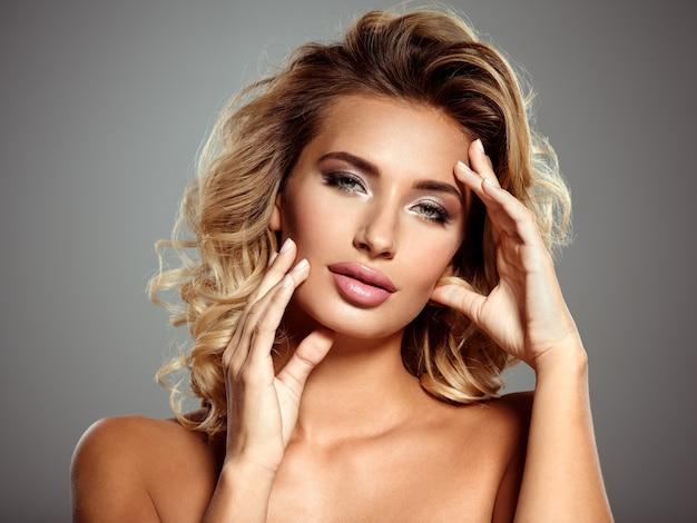 Zdjęcie pięknej blond kobiety z kwiatem. zbliżenie atrakcyjna zmysłowa twarz białej kobiety z kręconymi włosami. makijaż smokey eye.