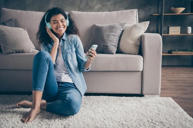 Zdjęcie pięknej ciemnej skóry falującej kobiety z zamkniętymi oczami trzymającej telefon nosić fajne nauszniki słuchanie nowego audio siedząc na podłodze w pobliżu kanapy swobodny dżinsowy strój salon w pomieszczeniu