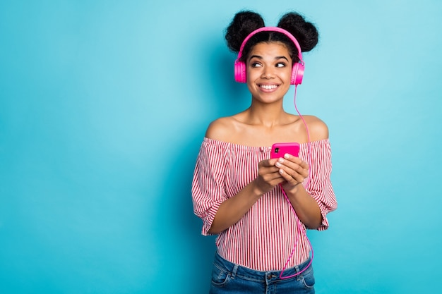 Zdjęcie pięknej ciemnej skóry pani trzymaj telefon słuchaj muzyki nowoczesne technologie słuchawki wygląd strony puste miejsce nosić czerwoną białą koszulę w paski poza ramionami izolowany niebieski kolor ściana