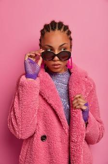 Zdjęcie pięknej ciemnoskórej czarującej dziewczyny odrywa wzrok, dotyka modnych okularów przeciwsłonecznych, zamyślona stoi w domu, nosi modne ciuchy, pozuje. koncepcja ludzie, moda i styl